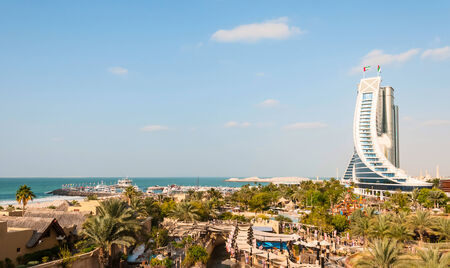 preceded: DUBAI, UAE - DECEMBER 10, 2013  Jumeirah Beach Hotel, preceded by beachfront - view from Wild Wadi water park  Well-known for its wave-shaped silhouette, remains one of the best recognizable landmarks of Dubai, UAE Editorial