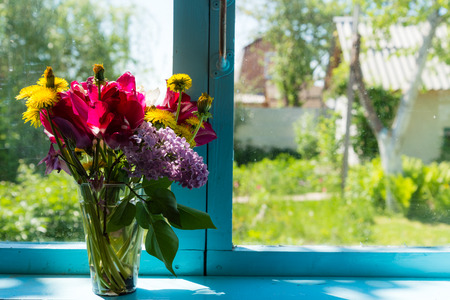 Bouquet of beautiful flowers on the blue window against garden photo