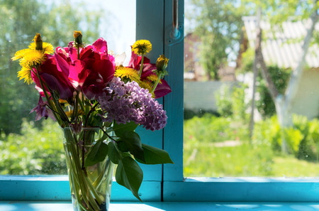 dacha: Bouquet of beautiful flowers on the blue window against garden Stock Photo