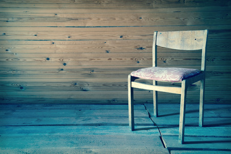 Vintage old wooden chair in grungy interior. Loneliness, estrangement, alienation concept. Toned image photo