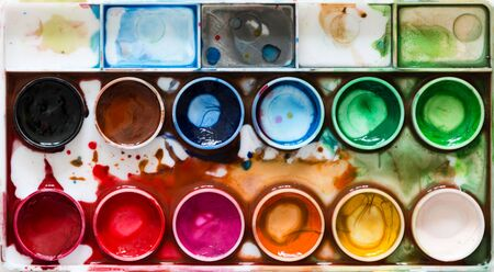 paint box: Tray of paints on spotted by paints paper Stock Photo