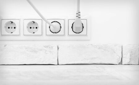 grounded plug: Electric plugs in a socket in the white interior