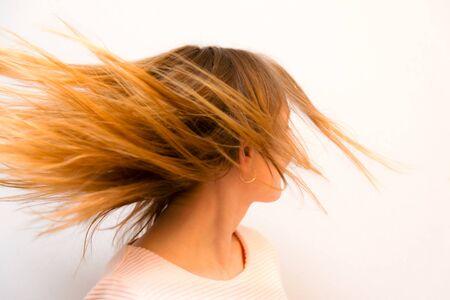 Nahaufnahme junge schöne Mädchen mit roten Haaren fliegen vor weißem Hintergrund