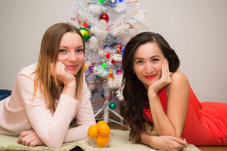 christmastime: Christmastime, two smiling young girls lying on the carpet in the background a christmas tree illuminated Stock Photo