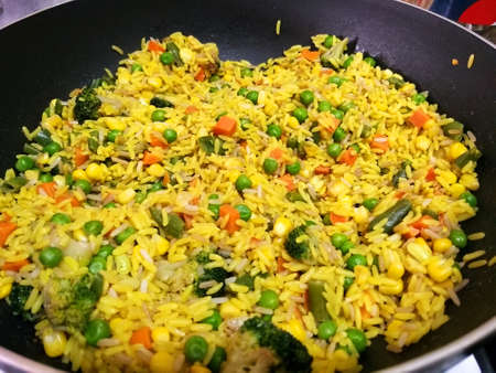 Close up view of a wok with saffron rice and vegetables just cooked. yellow, green, orange and red can be found in this colorful dish. Taken inside a kitchen, under a soft yellow light. Stock fotó