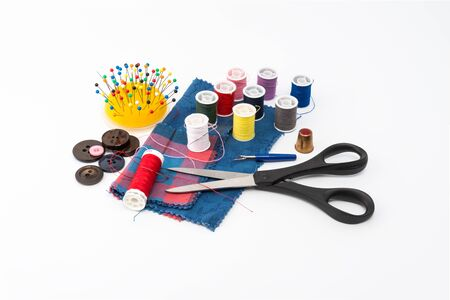 Thread, scissors, thimble and sewing pins. Thread is a type of yarn but similarly used for sewing.