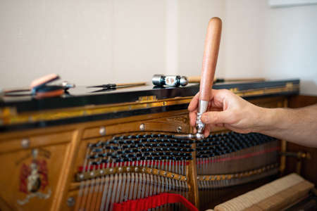 Technician, tuning a piano. Piano tuning is the act of adjusting the tension of the strings of an acoustic piano so that the musical intervals between strings are in tune.