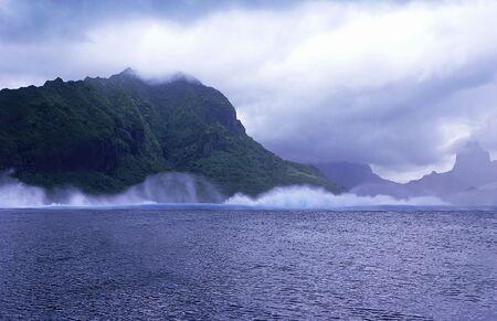 moorea: Waves crashing against mountain in Moorea, French Polynesia.