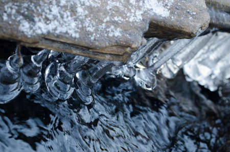 bell shaped: Bell shaped icicles hanging down over a river Stock Photo