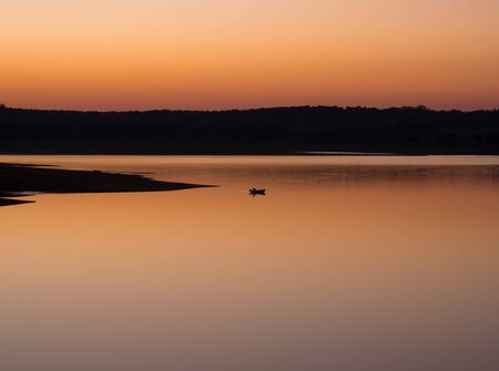 fishingpole: Man on boat at sunset in a lake