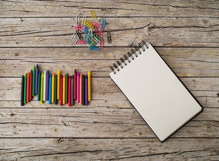 paper clips: colorful wax pencils, paper clips and notebook on wooden background