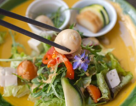 japanese quail: quail egg on chopsticks with japanese green vegetables salad on background