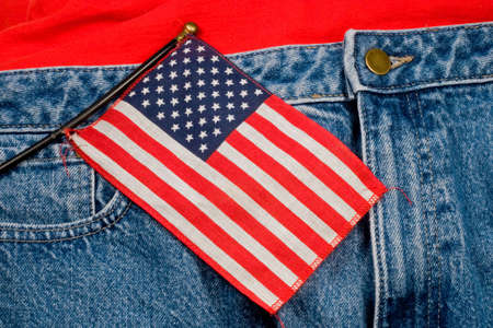 A small American flag against a pair of blue jeans and a t-shirt photo