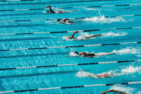 The swimmers competing at a high school meet strive for victory photo
