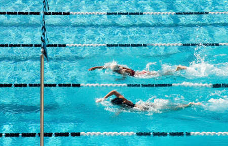 The swimmers competing at a high school meet strive for victory