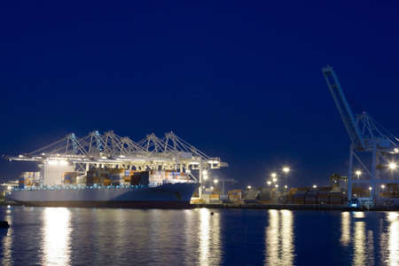 The containers and cargo of world trade move through a busy port Stock Photo
