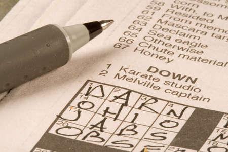 Krant kruiswoord raadsel wordt opgelost door de uitoefening van de hersenen Stockfoto
