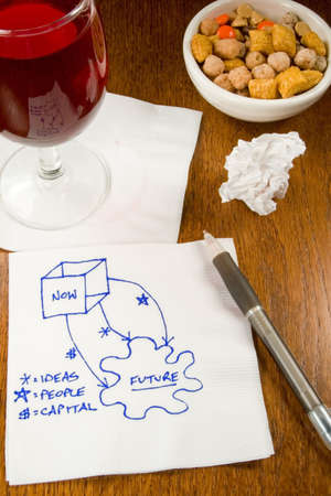 Ideas, charts, innovation on a cocktail napkin in a bar with wine and snacks