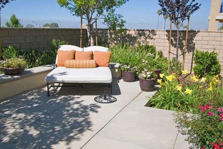 Achtertuin oase en voorst eden toevluchts oord met bloemen, lounge stoel en patio