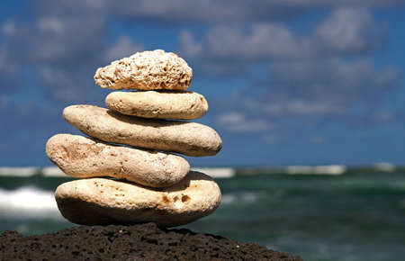 follower: White coral rocks stacked by a meditating zen follower Stock Photo