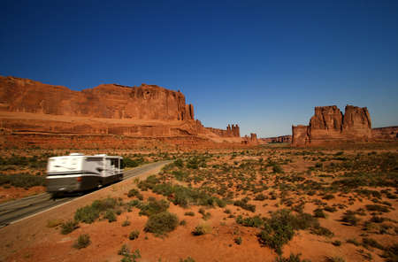 Summer vacation travelers tour through Arches National Park in Utah USA photo