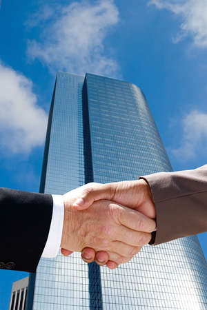 Businessman handshake against the towering skyscrapers of downtown Stock Photo - 5452436