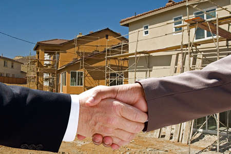 seller: Businessman handshake amongst a new housing construction project
