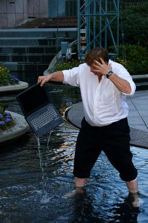Een laptop die door een zakenman in het water valt Stockfoto