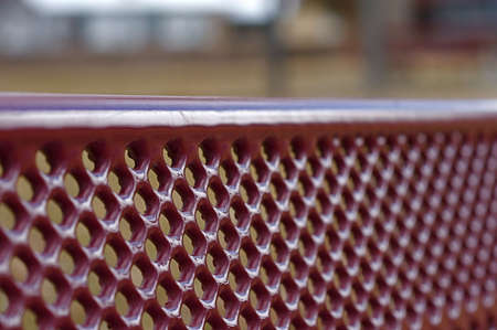 Shallow depth of focus on a red play ground bench
