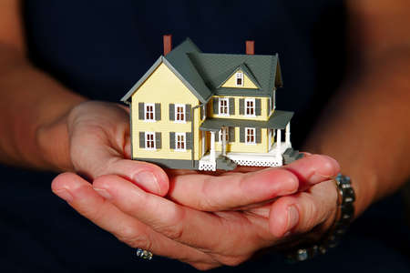 hand holding house: Woman holding a hand-made house model.