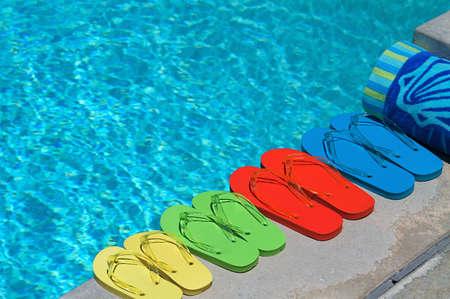 수영장으로 4 인 가족의 색깔의 flipflops