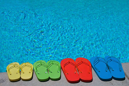 sandals: Colored flipflops of a family of four by the swimming pool