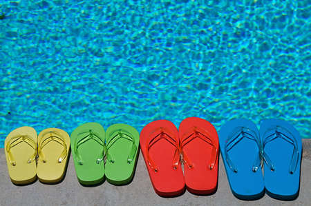 Colored flipflops of a family of four by the swimming pool photo