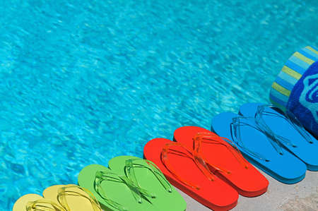 swimming shoes: Colored flipflops of a family of four by the swimming pool