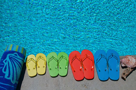 pool deck: Colored flipflops of a family of four by the swimming pool