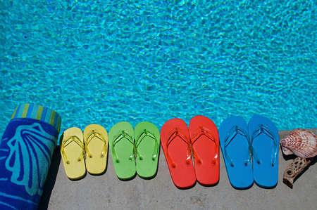 Gekleurde flip flops van een gezin van vier bij het zwembad