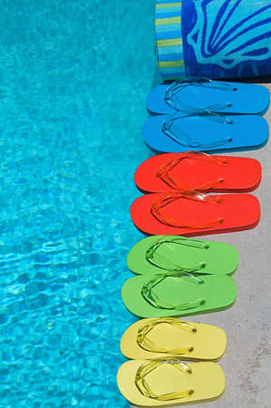Colored flipflops of a family of four by the swimming pool Stock Photo - 9050054