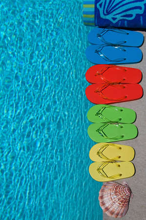 Colored flipflops of a family of four by the swimming pool Stock Photo - 9050065