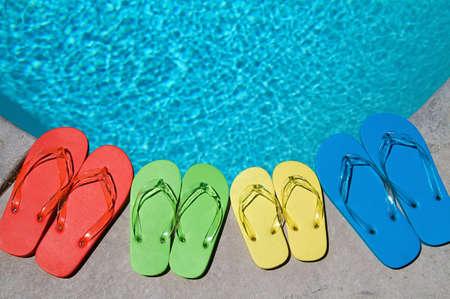 water shoes: Colored flipflops of a family of four by the swimming pool