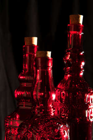 cutglass: Dark and moody red, cut-glass, decantor bottles with cork stopper Stock Photo