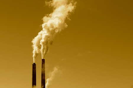 A tall smokestack spewing out dirty polluted smoke Фото со стока