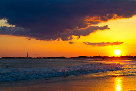 Sunset over the Cape May New Jersey Shore with the Lighthouse in the Distance over the crashing Waves photo