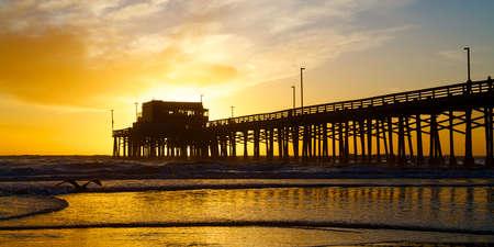 黄金のシルエットで日没ニューポート ビーチ カリフォルニア州桟橋