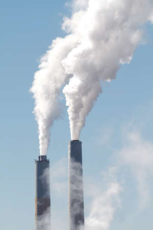 spewing: A tall smokestack spewing out dirty polluted smoke Stock Photo