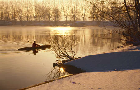 Oarsman on ice cold lake one morning in January
