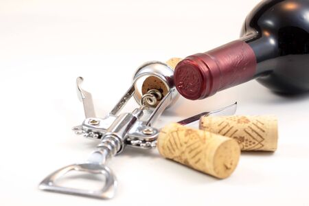 Isolated corks, red wine and corkscrew with white background photo