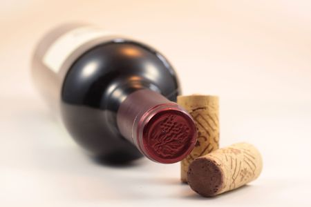 Isolated corks and red wine bottle with white background photo