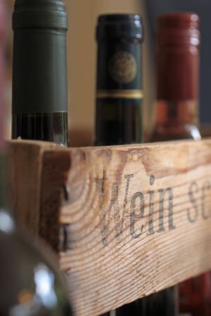 Old wooden wine box with many bottles photo