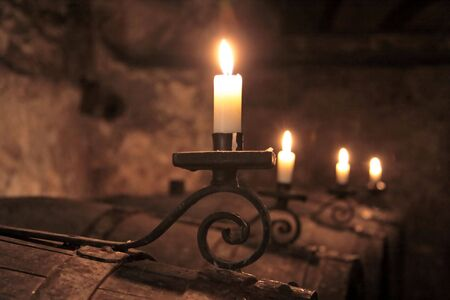 the architecture is ancient: Candles in wine-cellar on old wine barrels