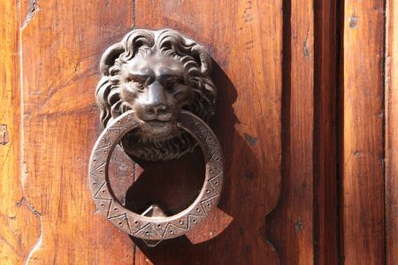 Door knockers lion on an old door in San Gimignano in Tuscany photo